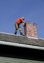 Man on a roof inspecting his chimney