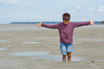 Young kid having fun with quicksand on the beach in front of Mon
