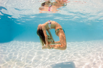 Underwater woman portrait wearing bikini in swimming pool.