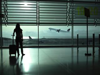 Mujer con maleta viendo despegar un avión