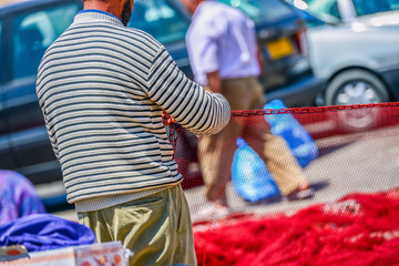 Sailor repairing the red fishing net