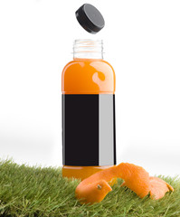 Orange juice in bottle with blank label on grass