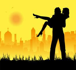 fidanzati che si abbracciano e città sullo sfondo