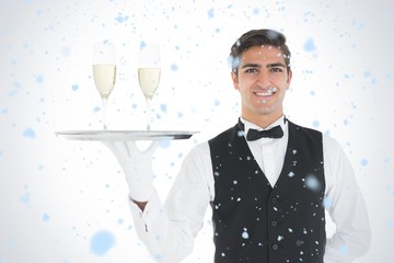 Smiling waiter holding a tray with champagne glasses