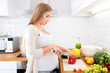 Pregnant woman at kitchen preparing salad - 69723843