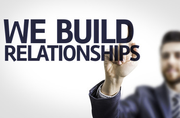 Business man pointing the text: We Build Relationship