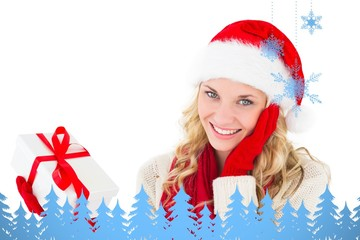Festive blonde smiling at camera holding present