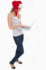 Portrait of a woman with a christmas hat using laptop