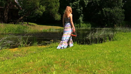 girl with long dress go along river in hand basket of fruit