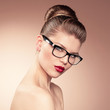 Beautiful young girl with retro hairdo in spectacles