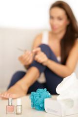 junge Frau auf Sofa mit Nagelschere