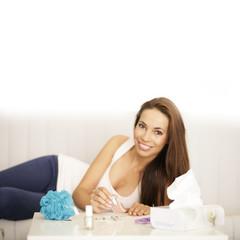 junge Frau auf Sofa mit Nagellack