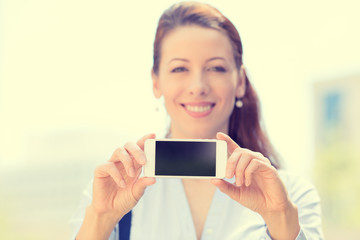 Female holding blank smart phone, focus on black screen