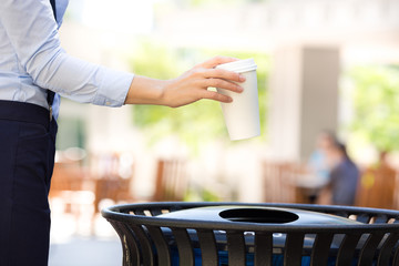 Image woman's hand throwing coffee cup in recycling bin