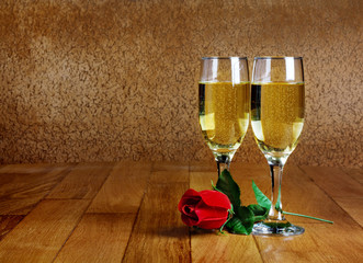 Two glasses of champagne with artificial red rose on wooden tabl