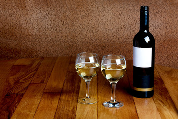 Bottle of white wine and two glasses on  wooden table top