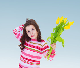Adorable little girl holding a bouquet of yellow tulips.