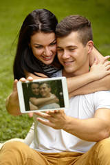 Couple Using Digital Tablet and Smiling While Sitting Close To E
