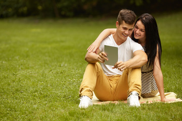 Couple using electronic tablet in summer park