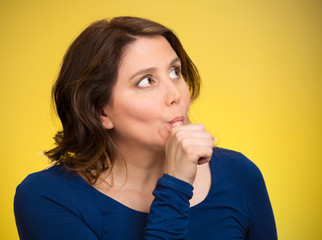 Woman with finger in mouth, sucking thumb, procrastinating
