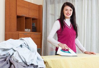 Happy  woman ironing  in home