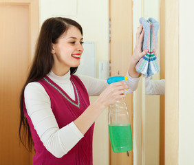 Happy brunette woman cleaning  mirror