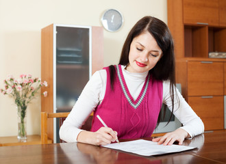 Smiling brunette woman filling in financial documents