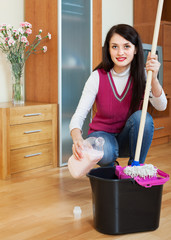 Smiling brunette woman washing  floor with detergent