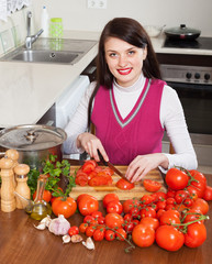 Happy brunette woman slicing tomatoes