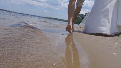 Newlyweds running along beach