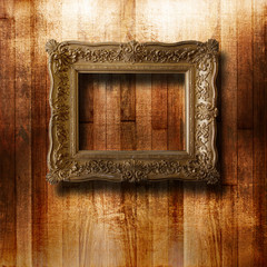 Old gilded picture frame for portrait on the scratched wooden wa
