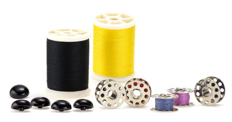 Sewing set with pool of thread,bobbins, and buttons.