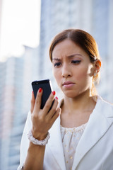 Portrait sad business woman typing sms phone street