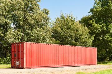 Ein grosser roter Seecontainer steht vor grünen Bäumen