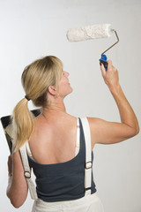 Female painter decorator using a paint roller
