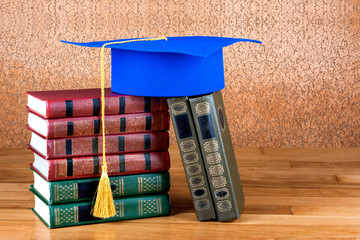 Graduation mortarboard on top of stack of books on wooden backgr