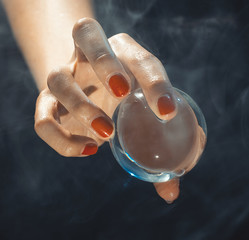 The hand holds a glass sphere