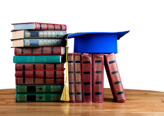 Graduation mortarboard on top of stack of books on white isolate