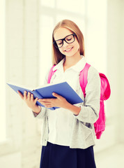 girl reading book at school