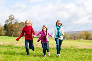 Mädchen rennen durch Herbst Park