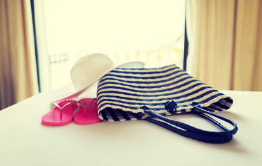 close-up of beach bag, hat and flip-flop on bed
