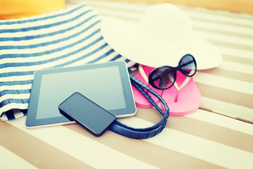 close up of tablet pc and smartphone on beach