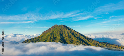 Mountain above the clouds from the rim of the Kawah Ijen volcano - 69735851