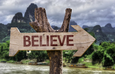 Believe wooden sign with a forest background