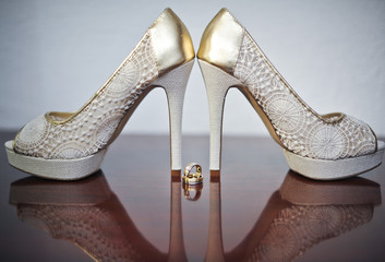 High heels wedding shoes and rings on table. Wedding accessories