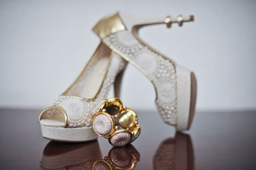 High heels wedding shoes and bracelet on table. Wedding