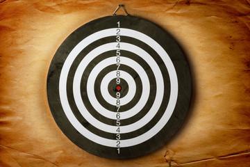 Vintage dart board on grunge dark wall