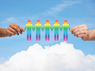 close up of hands holding paper chain gay people