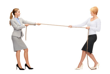 two smiling businesswomen pulling rope