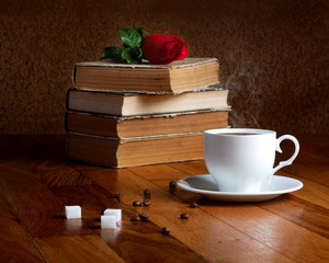Hot cup of fresh coffee on the wooden table and stack of books t